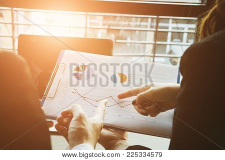 Business People Having A Meeting. Businessman & Businesswoman Working With Financial Plan Report At