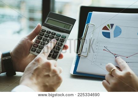 Business Adviser Working With Calculator & Financial Plan Report At Office. Accountant Doing Account