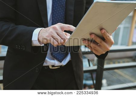 Businessman In Suit Holding Touchpad While Standing Outside Building. Young Asian Man Using Digital