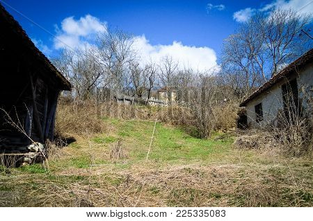 Old abandoned Serbian house with damaged facade plaster and roof tiles in old abandoned mountain village in Serbia