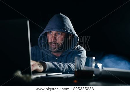 a male hacker is sitting in a dark room at the table and that something is typing and looking at the laptop