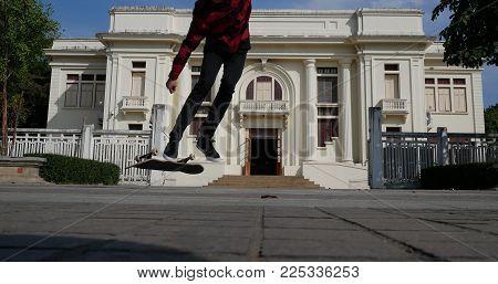 Skateboarder Skate & Jump Outdoors In Front Of Beige Building. Man On Skateboard. Sport Leisure Life
