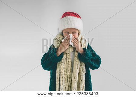 studio picture from a young girl with handkerchief. Sick child isolated has runny nose. Little Female model makes a cure for the common cold.