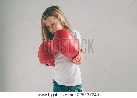 Cowardly funny young girl in red boxing gloves on white background
