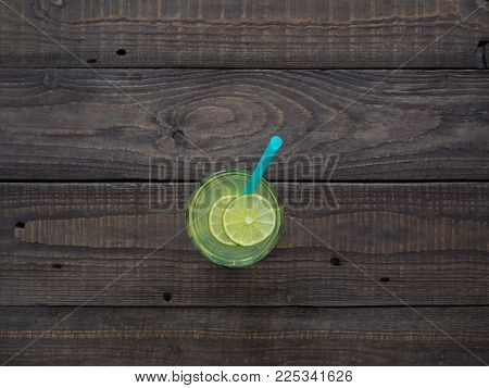 Large glass of natural lemonade stands on a wooden table