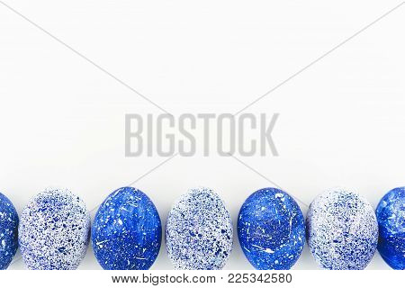 Blue Speckled Easter Eggs with copy space on white background. Flat lay. Top view