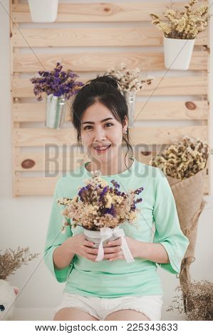 Young Beautiful Asian Woman Wear Light Green Shirt Hold Flowers In Her Hands In Morning Time With Na