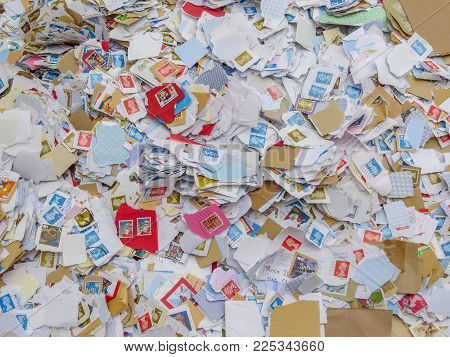WREXHAM, UK - MARCH 15, 2015: Kiloware, a large pile of used postage stamps torn from envelopes. Mostly British. Kiloware is a collection of stamps sold by weight usually to raise funds for charity.