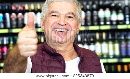 Satisfied Man Thumbs Up with Bottles on background