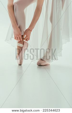 Low Section Of Ballerina Wearing Ballet Shoes, Isolated On White
