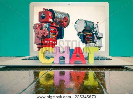the word CHAT on top of a laptop on a wooden floor  plus two robot toys on tin can phones
