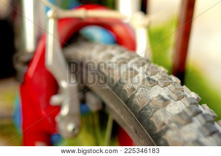 Dusty MTB wheel close-up, one part of bicycle wheel. Sport, activity and summer concept.