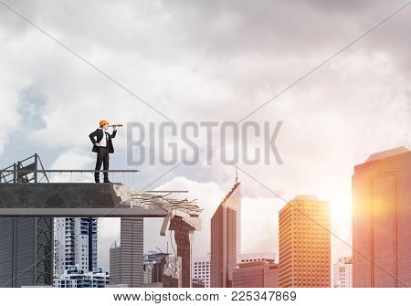 Young Engineer In Suit And Helmet Looking In Spyglass While Standing On Broken Bridge With Cityscape