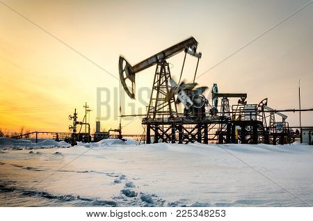 Pump jack, wellhead and pipeline during sunset in the oilfield. Winter period. Oil and gas concept. Toned. Motion blur.