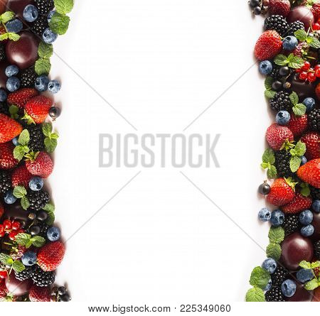 Mix berries on a white. Berries and fruits at border of image with copy space for text. Black-blue and red food. Ripe blackberries, blueberries, strawberries, red currants and plums on white background. Background berries. Various fresh summer berries. To