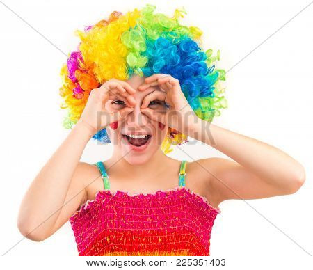 Cute little girl in clown wig using her hands as binoculars isolated on white background
