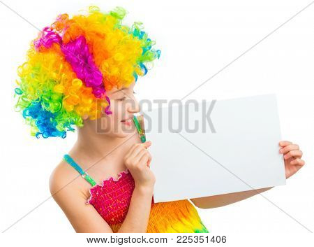 Young little girl in colourful clown wig holding white blank sheet of paper isolated on white background, copyspace