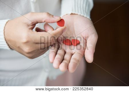 Female hands is holding red pils in heart shape Valentines concept. Health. Disease. Love. Illness.