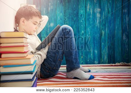 eight years old child reading a book at home. Boy studying on blue background