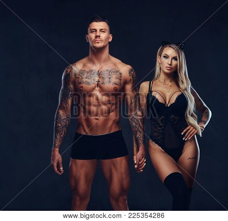Beautiful couple, handsome tattooed male and alluring girl in black underwear holding hands, posing in studio.