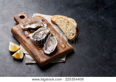 Opened oysters, ice and lemon on wooden board over stone table. With copy space