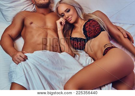 Sexy couple. Portrait of sexy husband and wife, relaxing in bed, honeymoon.
