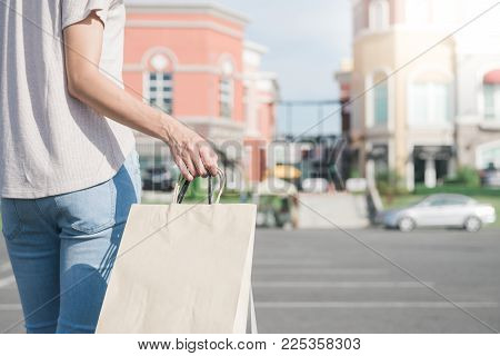 Close up of a young Asian woman shopping an outdoor flea market with a background of pastel bulidings and blue sky. Young woman smile with a colorful bag in her hand. Outdoor shopping concept.