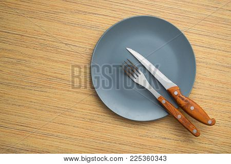 Metal Fork And Knife On A Wooden Table
