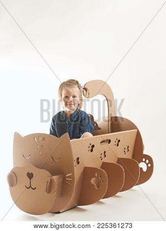 girl 5 years playing in a cardboard cradle.