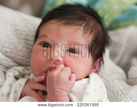 Close up of newborn infant baby sucking on fingers