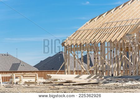 Hilltop wood frame house under construction near completed homes in Irving, Texas, USA. New two-story stick built, joist, timber frame panels and temporary struts. Pile of logs, plank, beam