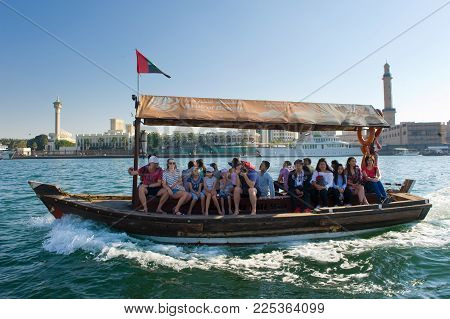 DUBAI, UNITED ARAB EMIRATES - JAN 02, 2018: Tourists on a boat a who go to the Deira old Souq station close to the City of gold in Dubai. It's a famous place visited by tourists.