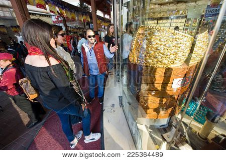 DUBAI, UNITED ARAB EMIRATES - JAN 02, 2018: Tourists are looking at the largest golden ring in the world, it weighs almost 64 kilograms. The ring is in the guinness book of records. It is located in the City of gold in Dubai.