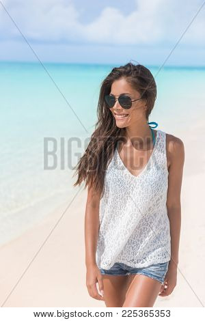 Summer woman relaxing walking on beach wearing sunglasses and jeans shorts, beach clothes. Happy Asian girl having fun during travel holidays vacation. Young cool woman enjoying vacation.