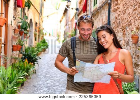 Europe travel tourists couple looking at map to find directions walking in old streets of spanish city Palma in Mallorca, Spain. Asian woman, Caucasian man on Cruise vacation during summer holidays.