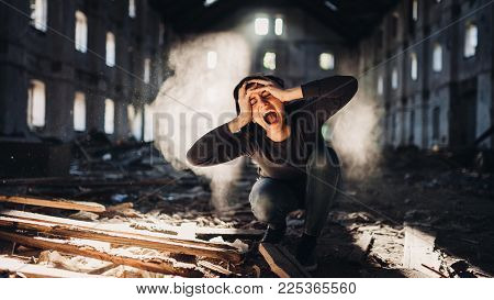 Sad depressed person in abandoned destroyed building crying.Emotional portrait.Mentally ill man with bipolar disorder and psychosis.Schizophrenia.Madness, crazy person.Voices in head.Tinnitus