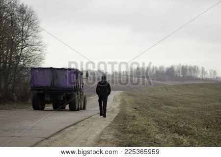 A sportsman is mooving away  on a higway with a tractor passing by in countryside landscape.