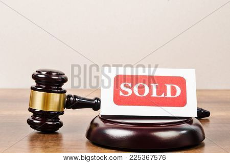 Sold Tag With Wooden Gavel On Wooden Table.