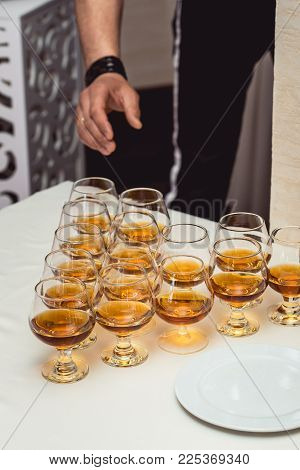 Mans hand taking a glass of alcohol. Pyramid of glasses of alcohol made in a pyramid for event party or wedding ceremony.