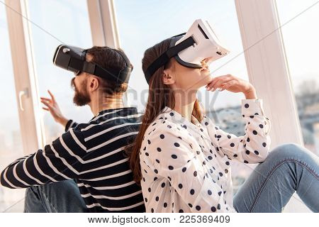 Immersive headset. Wistful meditative musing woman touching face while staring up and sitting near boyfriend