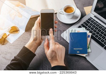 Female hand holding a smartphone. Planning a trip, buying tickets online. Top view