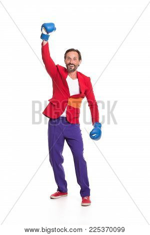 Male boxer in colorful clothes. Raising one hand and smiling.