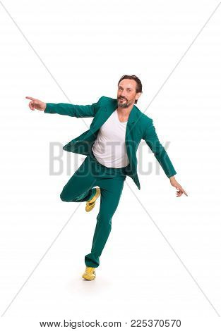 Careless man in nice green suit. Immitating flying.