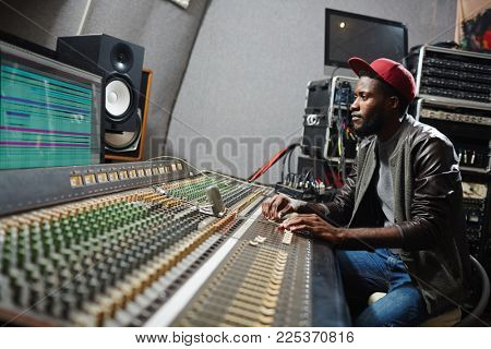 Young professional sitting by soundboard and mixing sounds while adjusting records