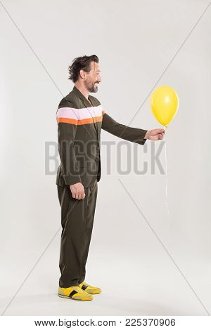 Careless man in black suit with red and white stripes. Holding yellow balloon.