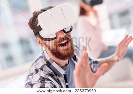 Upgraded VR technology. Gay fascinated optimistic man trying to touch VR objects and laughing