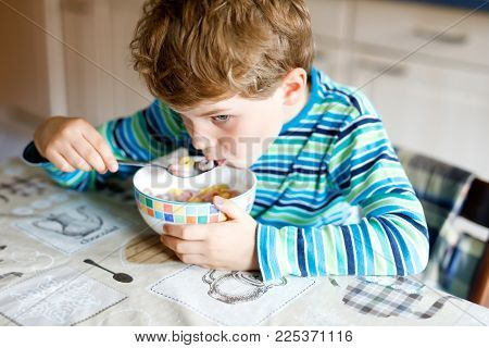 Adorable little blond school kid boy eating cereals with milk and berries for breakfast or lunch. Healthy eating for children, schoolkids. At school canteen or at home.