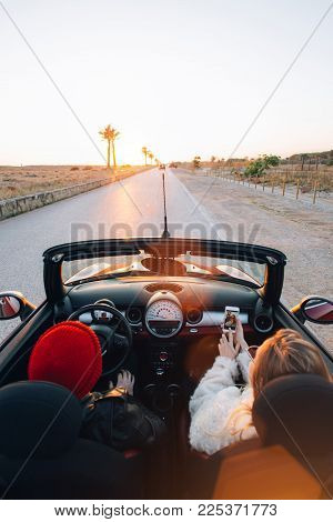 Happy and excited young couple rides in cute convertible cabriolet car into sunset on warm summer evening, girl social media blogger makes photo or video selfie on smartphone, digital lifestyle