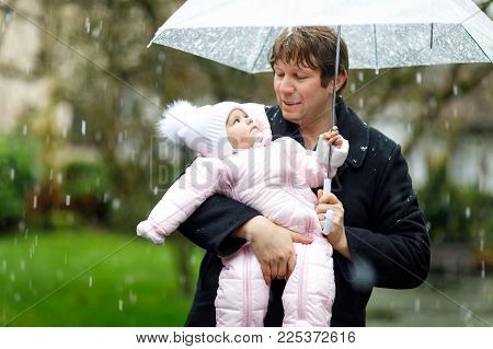 Cute little beautiful baby girl and young father on cold day with sleet, rain and snow. Happy smiling child in warm clothes, fashion stylish baby coat. Baby and dad with big umbrella