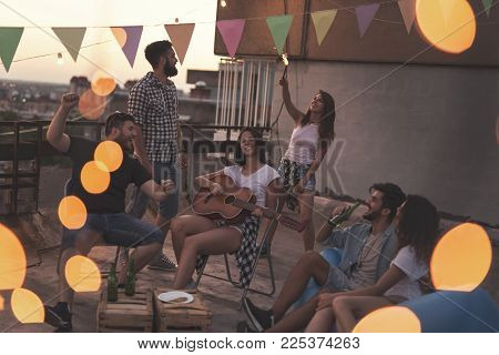 Young friends having fun at a summertime rooftop party, playing the guitar, singing, dancing and chilling out. Focus on the girls in the middle